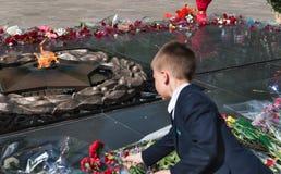 El colegial puso las flores al fuego eterno en el monumento Imagenes de archivo