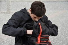 El colegial revuelve en su mochila, comprobando sus libros foto de archivo