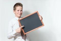 El colegial señala la pizarra negra limpia Imagen de archivo