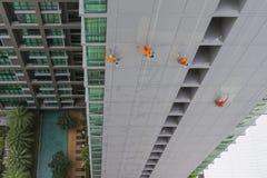 El colgante de pintores está pintando el alto edificio Imagen de archivo