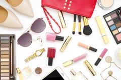 El collage femenino de los accesorios de la endecha plana con los zapatos, las gafas de sol y los cosméticos beige del tacón alto Imagenes de archivo
