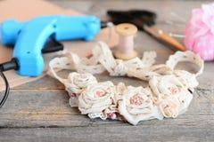 El collar de la tela, pega el arma caliente, tijeras, hilo, aguja, fieltro en una tabla de madera vieja Accesorio elegante de la  Foto de archivo