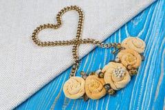El collar del trabajo hecho a mano encendido de una cadena de oro, presentado en la forma de un corazón es mentiras en un fondo d Imagenes de archivo