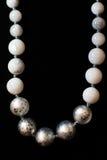 El collar empiedra las decoraciones blancas de la bola en un fondo negro Imagen de archivo libre de regalías