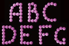El color de rosa marca en la tableta alfabeto Fotografía de archivo libre de regalías