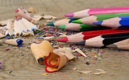 El color dibujó a lápiz virutas en fondo de madera fotos de archivo