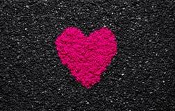 El color rosado plástico, el color de moda, corazón en el fondo texturizado negro, piedras, grava y tabla, aman el papel pintado, fotografía de archivo libre de regalías