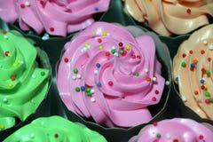El color rosado, verde y anaranjado de la torta de la taza con el azúcar redondeado colorido gotea en la crema fotos de archivo