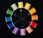 El color rueda hilos adentro de coser y los pernos imagenes de archivo