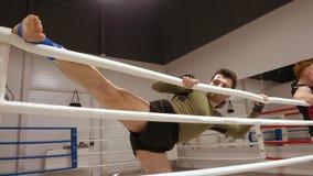 El combatiente atl?tico joven est? estirando sus piernas en el ringside en el club de la lucha