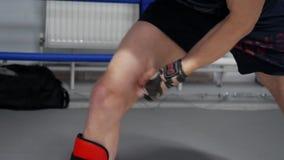 El combatiente calienta su pierna que da masajes a los músculos con las manos antes de entrenar metrajes