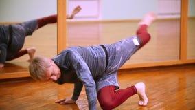 El combatiente caucásico masculino rubio realiza trucos marciales con los elementos de la danza en el gimnasio del deporte almacen de metraje de vídeo