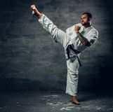 El combatiente del karate se vistió en un kimono blanco en la acción Fotos de archivo libres de regalías