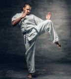 El combatiente del karate se vistió en un kimono blanco en la acción Fotos de archivo