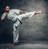 El combatiente del karate se vistió en un kimono blanco en la acción Foto de archivo