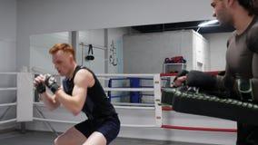 El combatiente está golpeando los mitones con el pie en las manos del coche en ringside tiene un entrenamiento personal almacen de metraje de vídeo