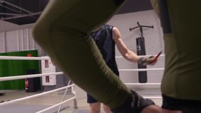 El combatiente está saltando en la cuerda de salto en ringside, entrenamiento con el instructor personal metrajes