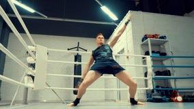 El combatiente joven profesional est? calentando antes de entrenar en ringside en club de la lucha