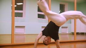El combatiente masculino realiza los trucos marciales, retroceso por el pie, con los elementos de la danza en el gimnasio almacen de video