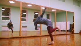 El combatiente masculino realiza trucos marciales con los elementos de la danza en el gimnasio del deporte delante del espejo metrajes
