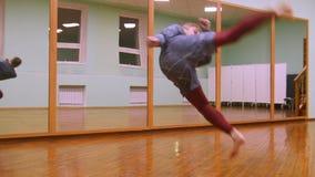 El combatiente masculino rubio realiza trucos marciales con los elementos de la danza en el gimnasio del deporte metrajes