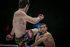 El combatiente mezclado atleta de los artes marciales pega su pie en la cabeza de su opositor Imagen de archivo