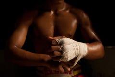 El combatiente muscular que ata la cinta alrededor de su mano Imagen de archivo libre de regalías