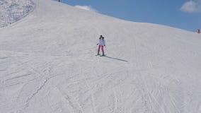 El comenzar y esquiador inseguro de la mujer que esquían abajo de la cuesta de montaña almacen de video