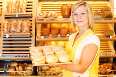 El comerciante de la panadería presenta los buñuelos Foto de archivo