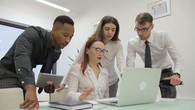 El comerciante de sexo femenino joven está presentando a sus colegas multiethnical los resultados del estudio de mercados digital almacen de video