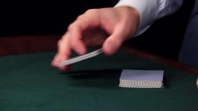 El comienzo del crupié mezcla las tarjetas, demostraciones una en la tabla en el casino almacen de metraje de vídeo