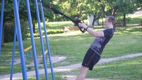 El comienzo del hombre intenso levanta el ejercicio con los lazos de la aptitud en un parque cantidad lenta de 4K MES metrajes