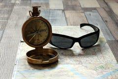 El compás y las gafas de sol miente en un mapa Imagen de archivo libre de regalías
