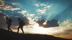 El compa?ero de equipo de ayuda del escalador subir, el hombre con la mochila alcanz? hacia fuera una mano amiga a su amigo Amigo almacen de metraje de vídeo