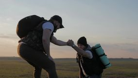 El compa?ero de equipo de ayuda del escalador subir, el hombre con la mochila alcanz? hacia fuera una mano amiga a su amigo Amigo metrajes