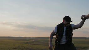 El compa?ero de equipo de ayuda del escalador subir, el hombre con la mochila alcanz? hacia fuera una mano amiga a su amigo Amigo almacen de video