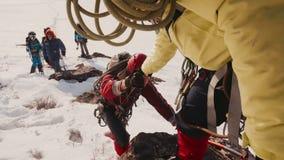 El compa?ero de equipo lleva a cabo hacia fuera su mano que sube para arriba al lado del escalador de monta?a, ayud?ndole a subir almacen de video
