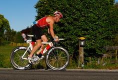 El competidor completa un ciclo en el acceso de Tauranga medio Ironman Foto de archivo libre de regalías