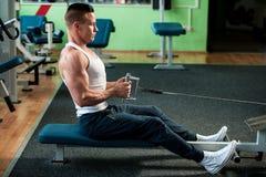 El competidor de la aptitud de Phisique se resuelve en pesas de gimnasia de elevación del gimnasio Fotografía de archivo libre de regalías