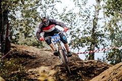 El competidor masculino del atleta cuesta abajo monta en bosque Imagenes de archivo