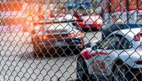 El competir con de coche deportivo del motor en la carretera de asfalto Visión desde la red de la malla de la cerca en el coche b Imágenes de archivo libres de regalías
