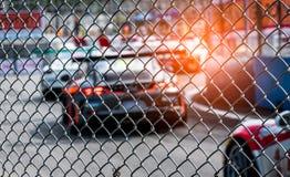 El competir con de coche deportivo del motor en la carretera de asfalto Visión desde la red de la malla de la cerca en el coche b Imagen de archivo libre de regalías