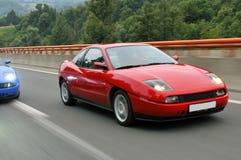 El competir con de coches de adaptación abajo de la carretera Fotos de archivo