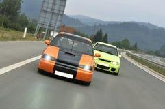 El competir con de coches de adaptación abajo de la carretera Fotos de archivo libres de regalías