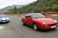 El competir con de coches de adaptación abajo de la carretera Imagenes de archivo