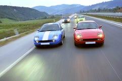 El competir con de coches de adaptación abajo de la carretera Imagen de archivo