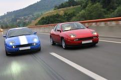 El competir con de coches de adaptación en la carretera Imagen de archivo libre de regalías