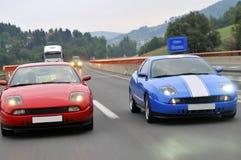 El competir con de coches de adaptación en la carretera Imágenes de archivo libres de regalías