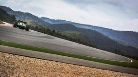 El competir con en la pista entre las colinas en un coche de carreras de la fórmula Imagenes de archivo