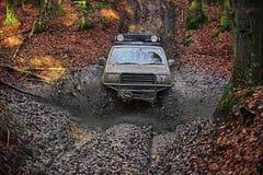 El competir con en los coches campo a través SUV cubrió con el fango pegado en suciedad en la trayectoria Foto de archivo libre de regalías